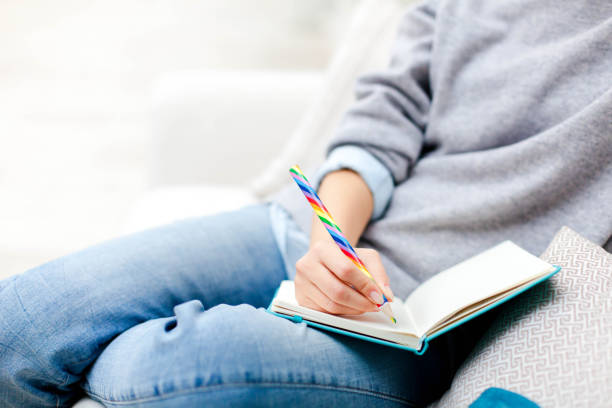 Female hand with rainbow pencil is writing goals in notebook. Freelancer is working in cozy place. Girl is planning and dreaming. Young woman is sitting on comfortable sofa. Close up. stock photo
