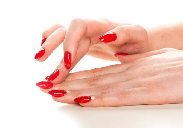 female hand with red manicure applying cream on cuticle - cuticle stock pictures, royalty-free photos & images