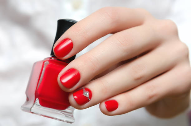 Female hand with red nail design holding nail polish bottle stock photo