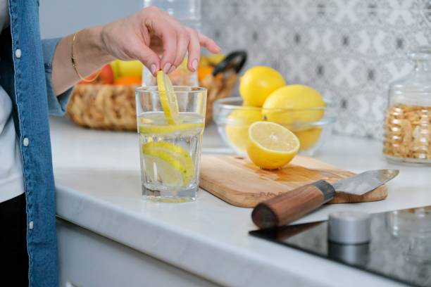 Mutfakta limon dilimi ile Kadın el, limon ile köpüklü su ile stok fotoğrafı