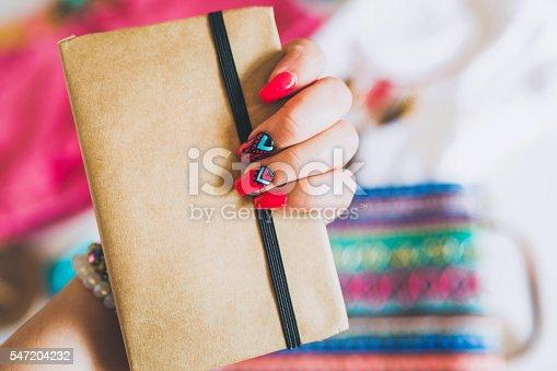 istock Female hand with stylish colorful boho nails holding notes 547204232