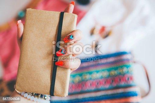 istock Female hand with stylish colorful boho nails holding notes 547204508