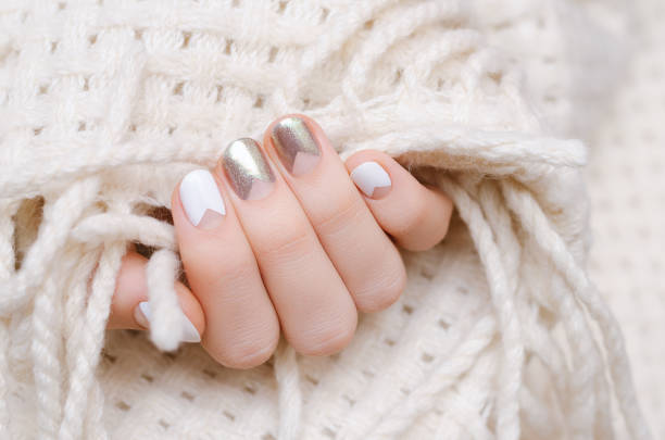 Female hand with white and silwer nail design stock photo