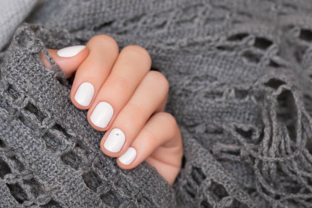 Female hand with white nail design, close up. stock photo
