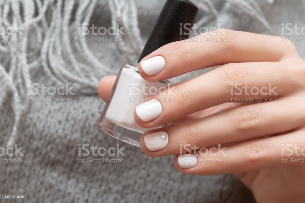 Mano Femenina Con Diseño De Uñas Blancas Sosteniendo La