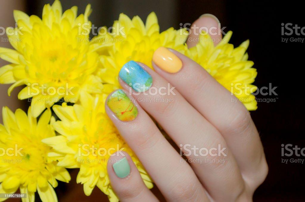 Mano Femenina Con Diseño De Uñas Amarillas Sosteniendo Flor