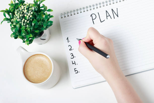 Female hand writes a plan in a notebook, goal setting concept stock photo