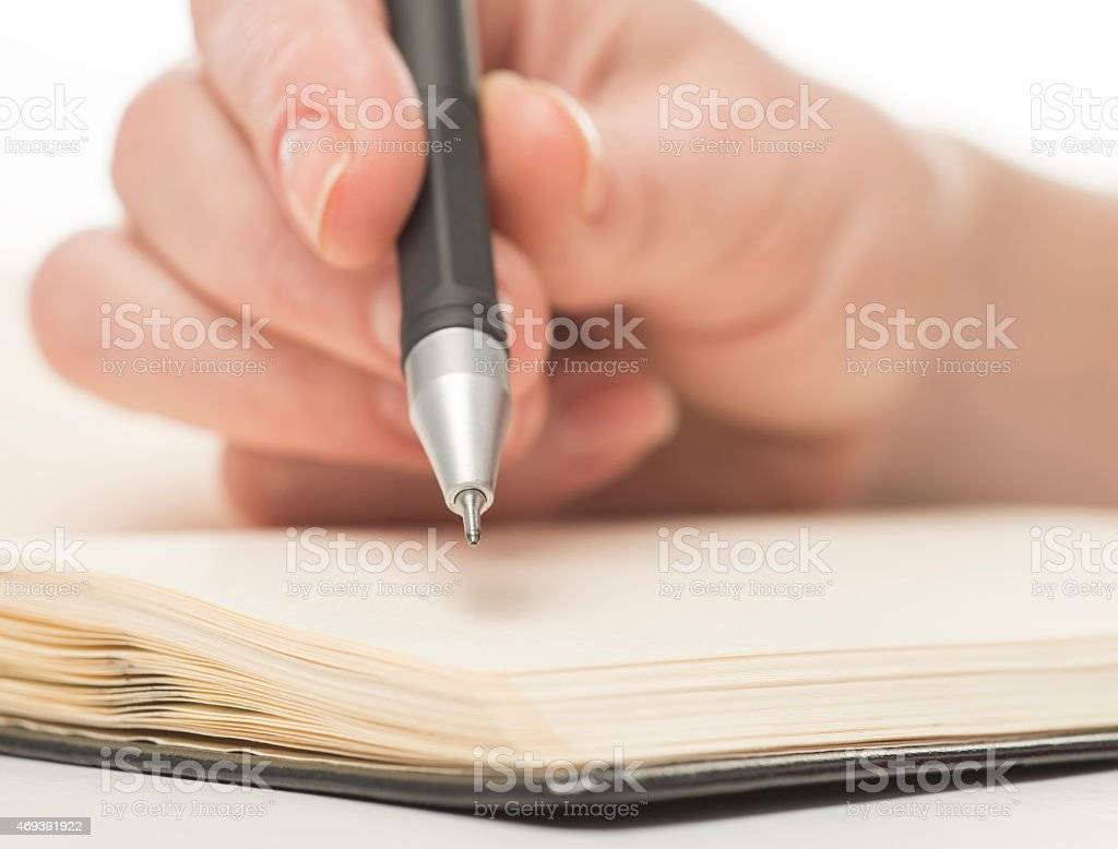 Female hand writing in notebook stock photo