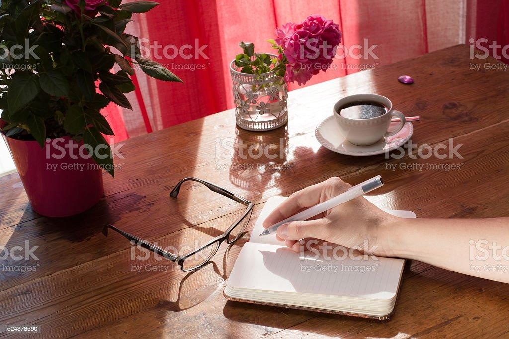 Feminino mão escrevendo no bloco de vintage Observação - foto de acervo