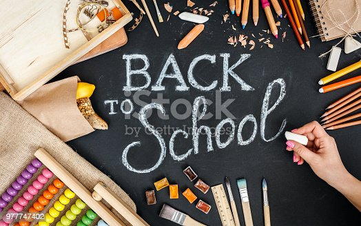 istock Female hand writing on blackboard with chalk. Back to school concept in warm colors. Top view. 977747402