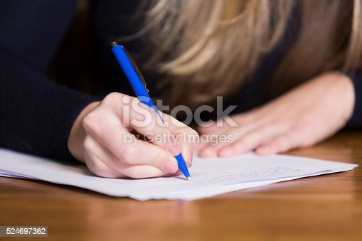 Close up of woman's hand writing on paper with a pen