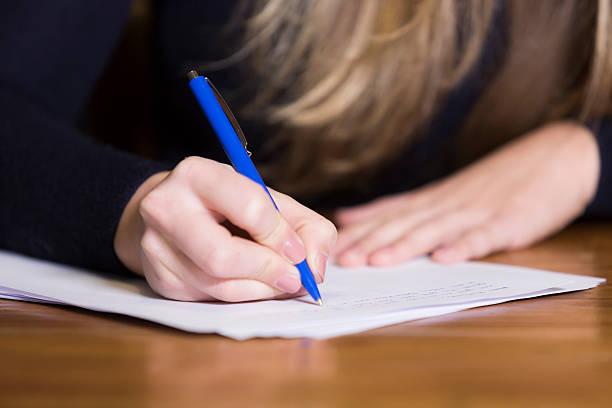 weibliche hand schreiben auf papier - schreibunterricht stock-fotos und bilder