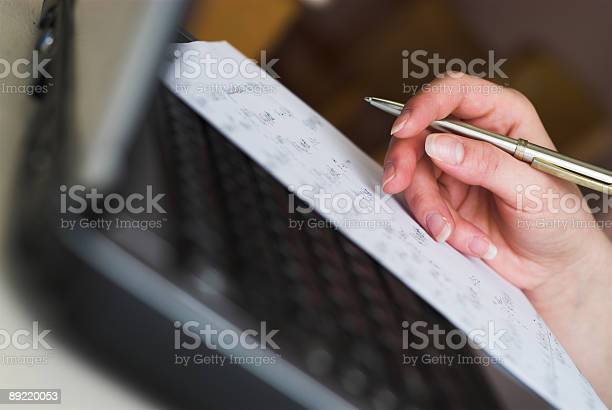 Female Hand Writing With Pen On Paper Atop A Laptop Stock Photo - Download Image Now
