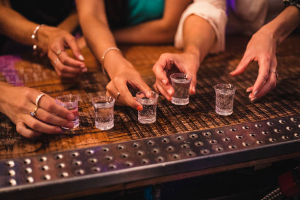 Female Hands about to Pick up Shot Glass Women about to pick up some shot glasses for their night out. tequila shot stock pictures, royalty-free photos & images