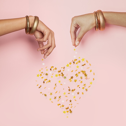 Female hands and falling confetti star. Heart on pink background