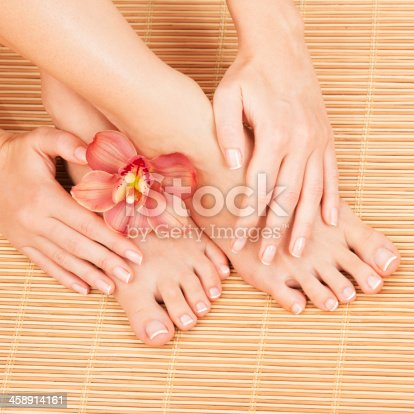 istock Female hands and feet on a bamboo mat with an orchid 458914161