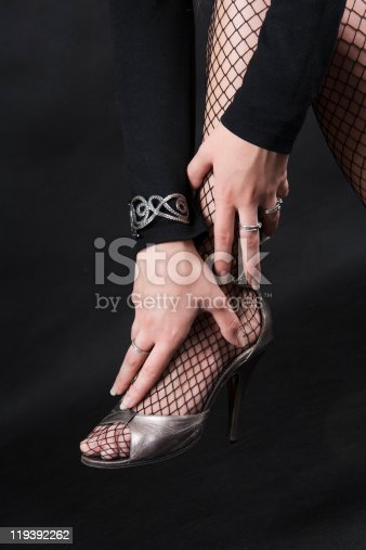 157582133 istock photo Female hands and foot on a heel 119392262