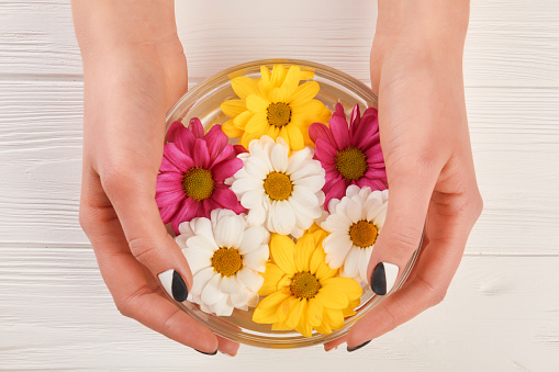 istock Female hands and manicure bath with flowers. 979640354