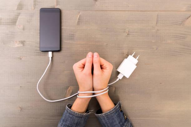 mani femminili e smartphone. mani della donna intrappolate e avvolte ai polsi con cavo del cellulare come manette. dipendenza da internet e social network - assuefazione foto e immagini stock