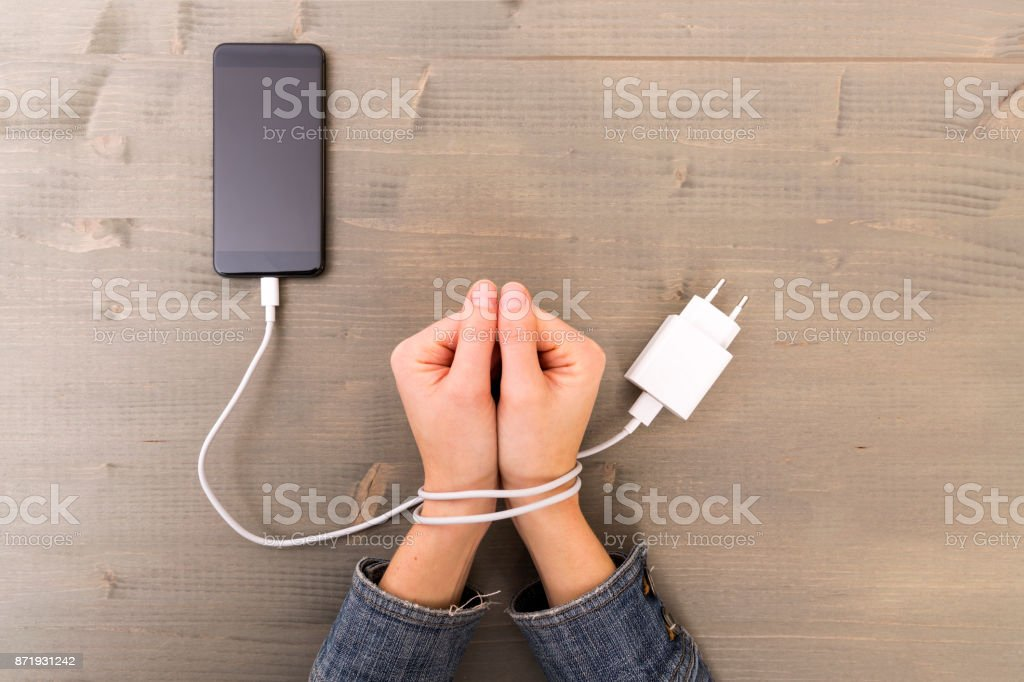 Female hands and smartphone. Woman's hands trapped and wrapped on wrists with mobile phone cable as handcuffs. Addiction to internet and social networks stock photo