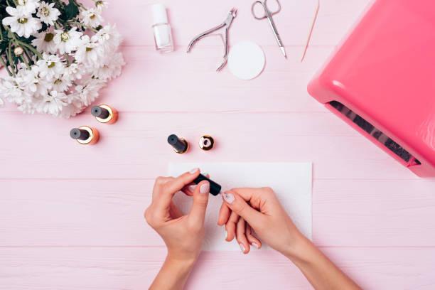 mãos femininas aplicam goma laca durante procedimento de manicure - manicure - fotografias e filmes do acervo