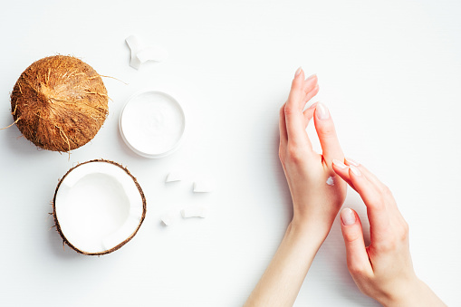 1151624350 istock photo Female hands applying coconut cream on white background. Coconut organic cosmetics, oil, lotion for hand skin care, natural moisturizer, health and beauty concept. Flat lay, top view 1221025294