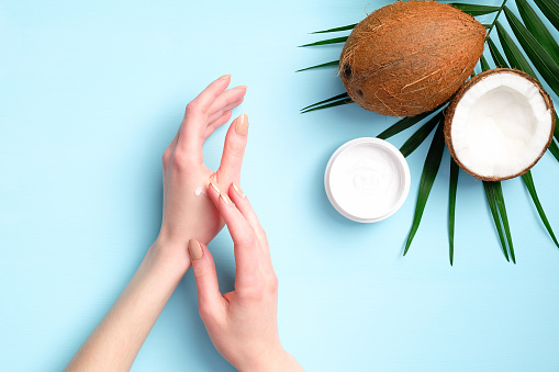 1151624350 istock photo Female hands applying organic cosmetics cream with coconut oil, top view. Skincare, body and hair treatment concept. 1226419762