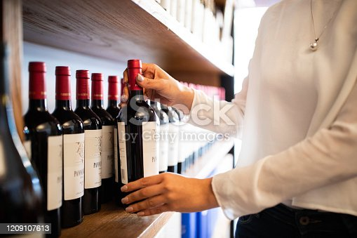 Close-up of female hands arranging wine bottles on shelf at wine shop.  Woman employee at a wine store organizing the bottles on a stand.