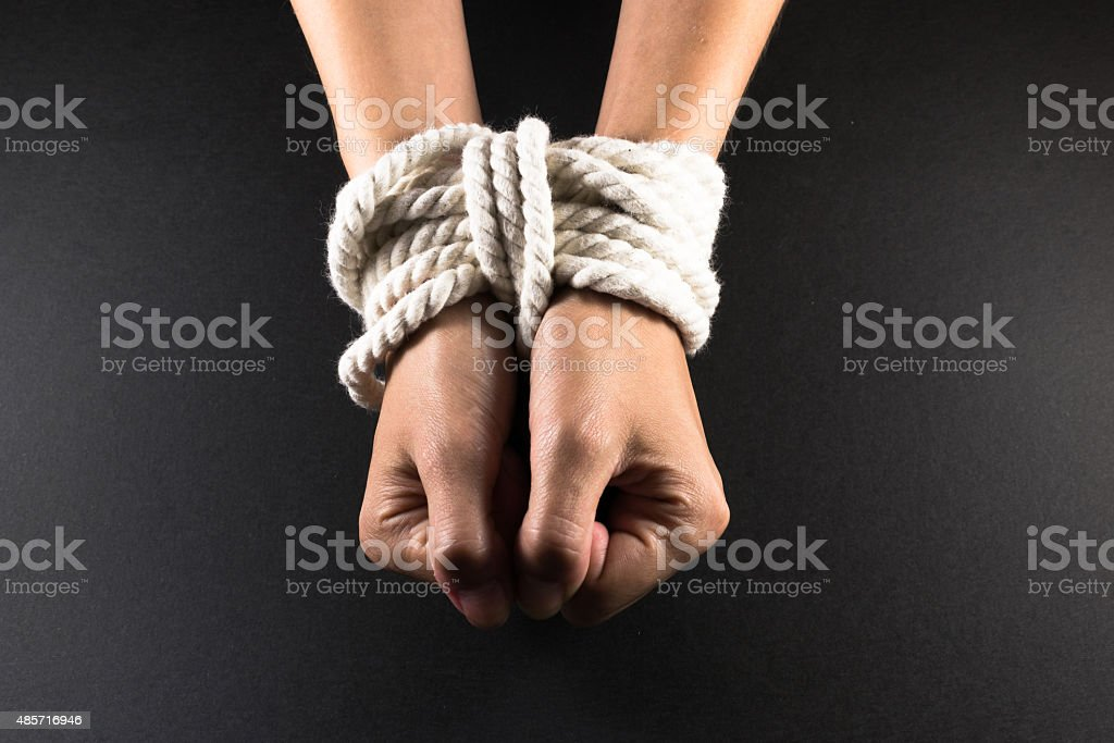 Female Hands Bound in Bondage with Rope stock photo