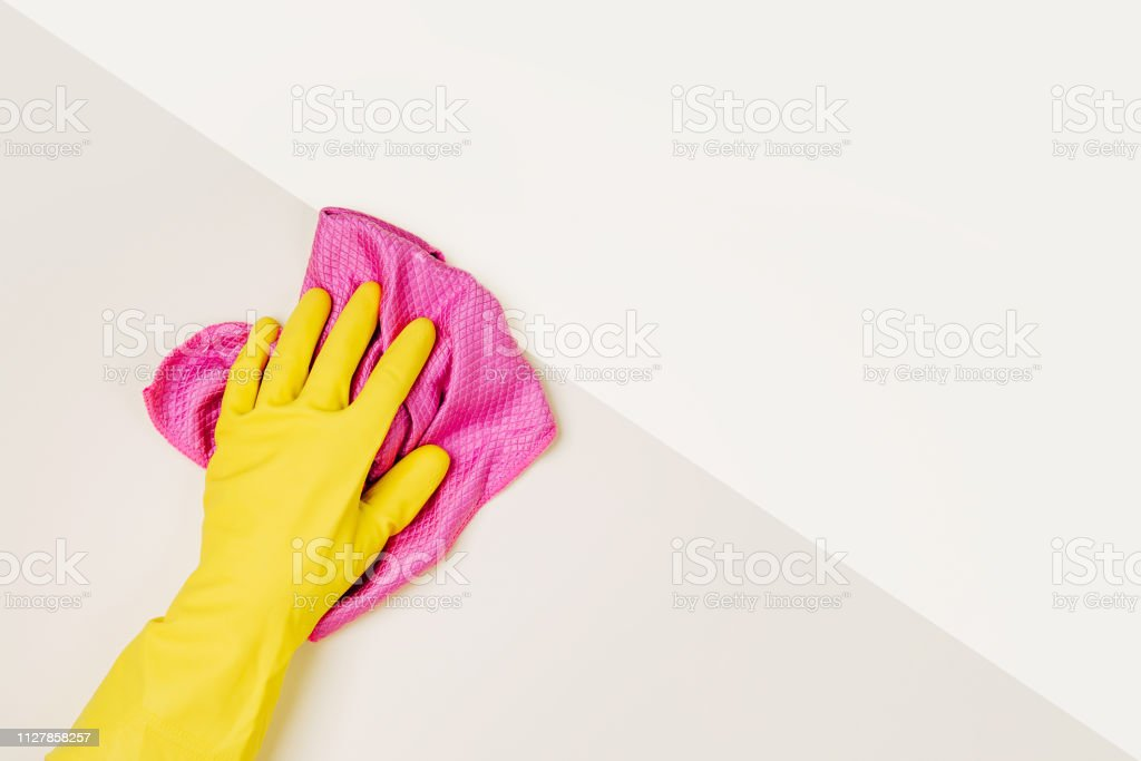 Female hands cleaning on pale yellow background. Cleaning or...