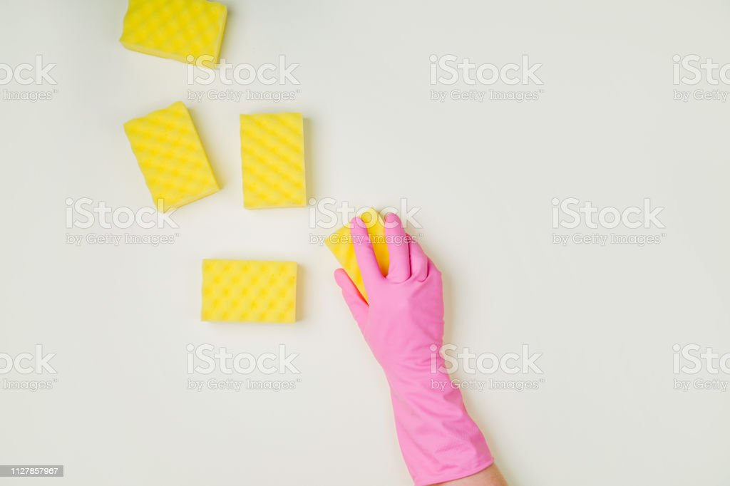Female hands cleaning with sponge on yellow background. Cleaning or...