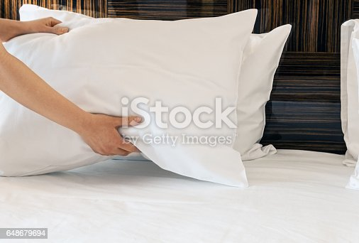 istock female hands corrected pillow on the bed 648679694