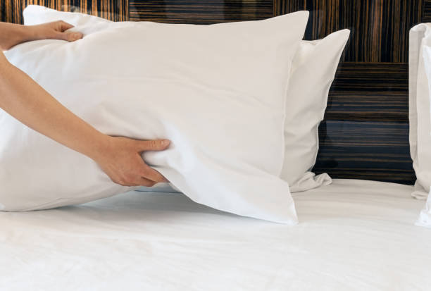 female hands corrected pillow on the bed stock photo