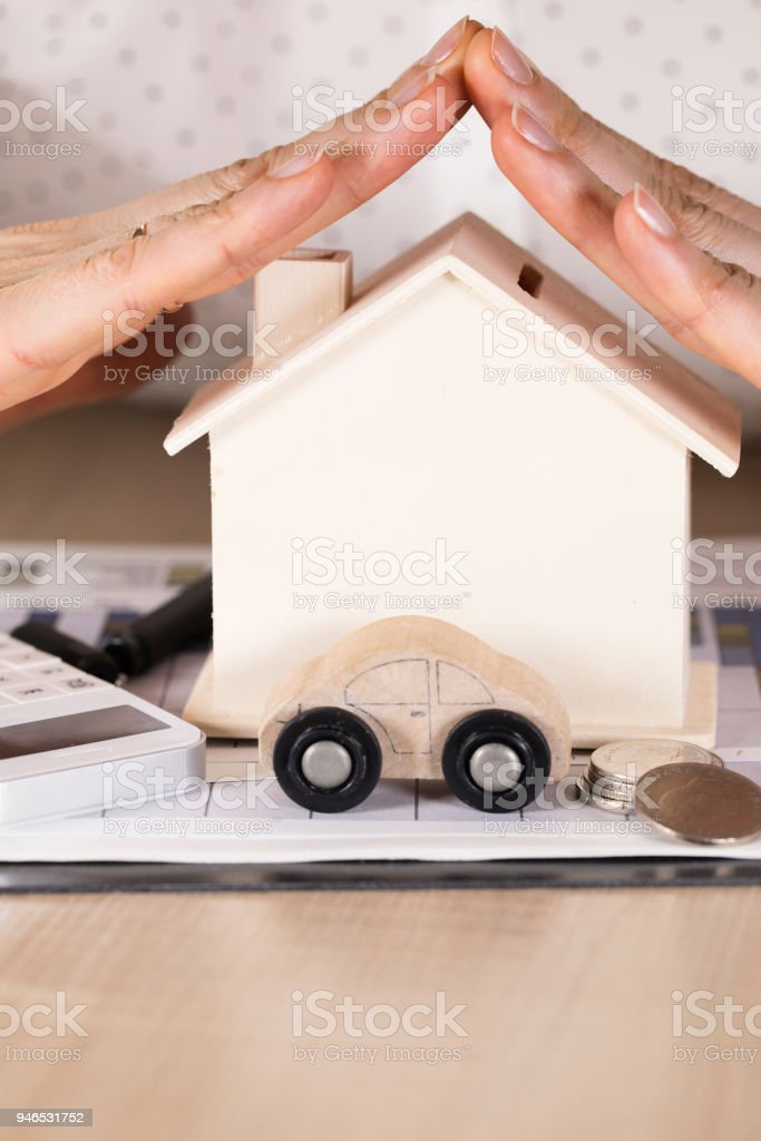 Female hands cover small wooden house. stock photo