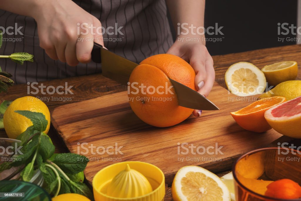 Female hands cutting citrus fruits on wooden board royalty-free stock photo