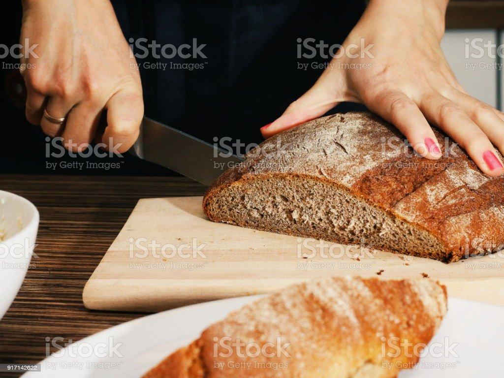 Female hands Cutting dark Bread on a wooden board stock photo