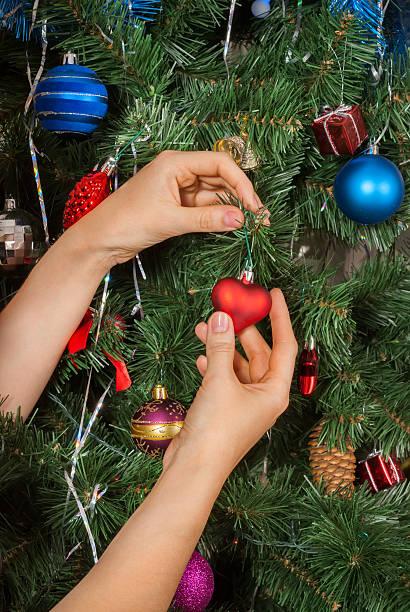 Female hands decorating christmas tree stock photo