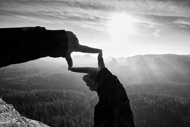 Female hands do frame gesture. Deep misty valley bellow cliff. stock photo