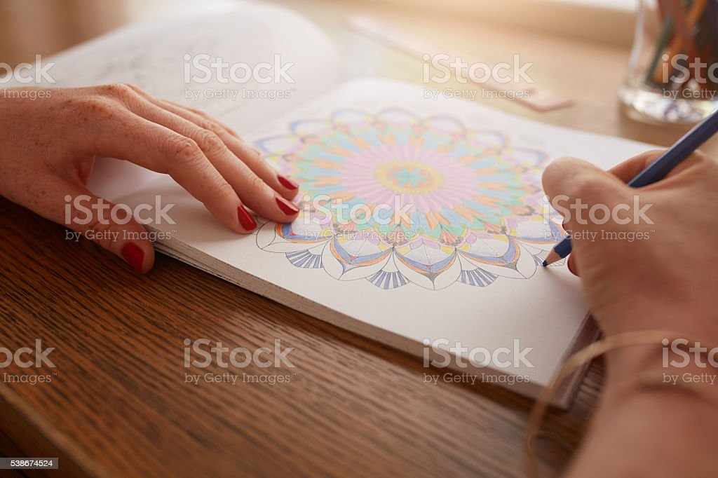 Female hands drawing in adult coloring book stock photo