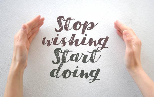 """weibliche hände, die text-zitat """"stop wish doing"""" auf weißem hintergrund einschließen - handschriftliche typografie stock-fotos und bilder"""