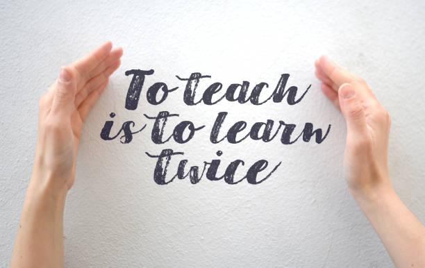 """weibliche hände, die text zitieren """"zu lehren ist, zweimal zu lernen"""" auf weißem hintergrund - handschriftliche typografie stock-fotos und bilder"""