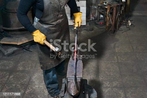 istock female hands forge a hot metal billet on the anvil in a traditional forge 1211171868