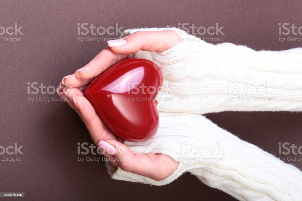 Female hands giving red heart, isolated on gold background, christmas winter love stock photo