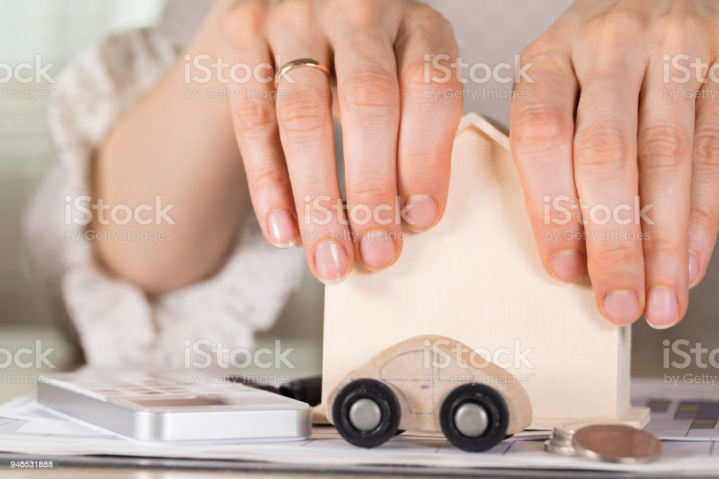 Female hands grasp small wooden house. stock photo