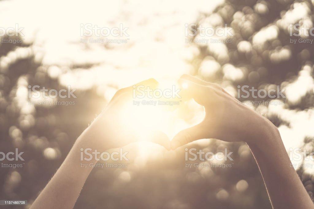 Female hands heart shape on nature bokeh sun light flare and blur...