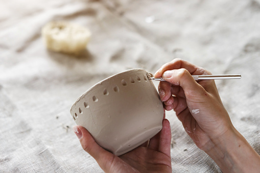 Female hands hold a bowl for casting clay products