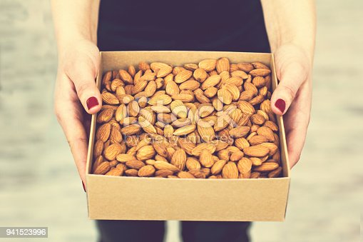 istock Female hands hold a box of nuts and dried fruits. 941523996