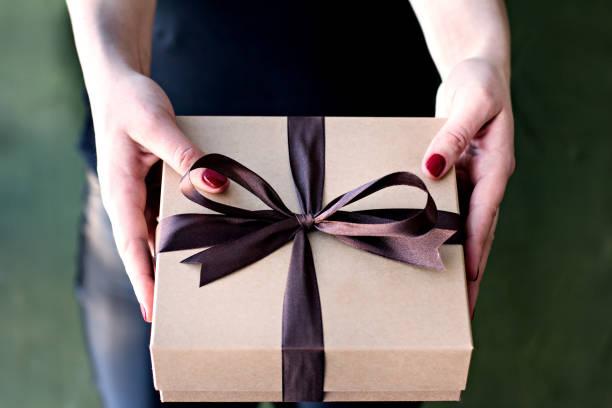 weibliche hände halten eine gestaltete box mit einem geschenk. - bastelkarton stock-fotos und bilder