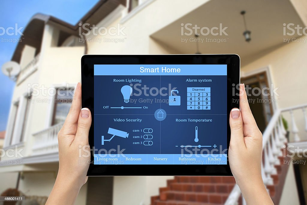 Female hands hold a tablet with system smart house stock photo