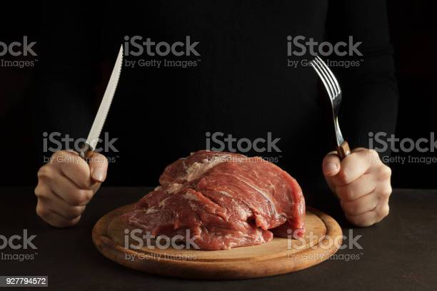 Female hands hold fork and knife and ready to eat raw meat on the wooden cutting board on dark background. Nonvegetarian concept, copy space.